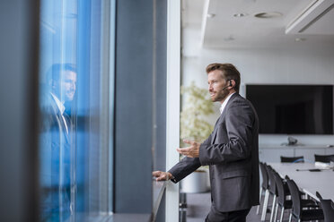 Relaxed businessman with bluetooth headset standing in his office looking out of the window - DIGF02704