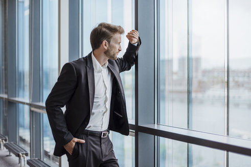 Businessman standing in office looking out of the window - DIGF02707