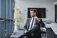 Businessman sitting in conference room looking out of the window - DIGF02710