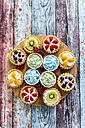 Mini pies with whipped cream garnished with different fruits - SARF03353