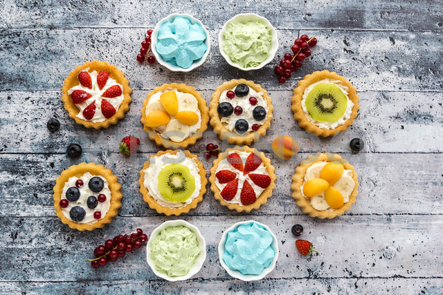 Mini pies with whipped cream garnished with different fruits - SARF03356