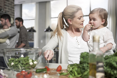 Mother holding baby preparing a healthy meal in kitchen - ZEF14431