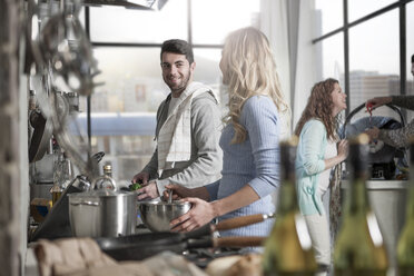 Couple preparing food in kitchen with family in the background - ZEF14443