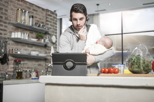Father with headset and tablet in kitchen holding baby - ZEF14458
