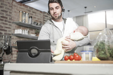 Father with headset and tablet in kitchen holding baby - ZEF14461