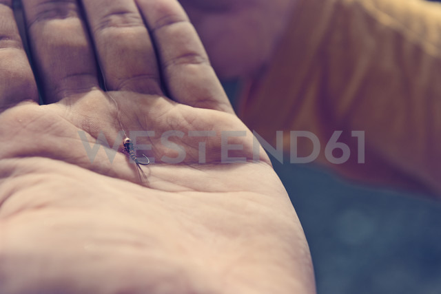 Close-up of fishhook in hand - BMAF00319