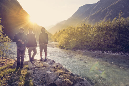 Slovenia, Bovec, three friends at Soca river at sunset - BMAF00331