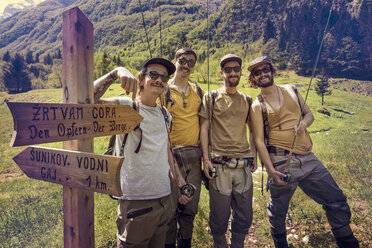 Slovenia, Bovec, four anglers posing at signpost on meadow near Soca river - BMAF00340