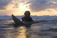 Indonesia, Bali, surfer in the ocean at sunrise - KNTF00875