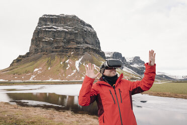 Iceland, man wearing Virtual Reality Glasses in nature - RAEF01902