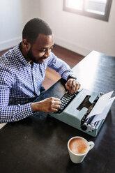 Young man at desk using typewriter - GIOF03134