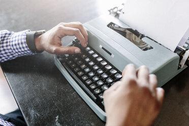 Close-up of man at desk using typewriter - GIOF03137