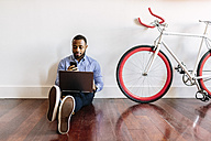 Man sitting on wooden floor with laptop and cell phone and bicycle next to him - GIOF03146