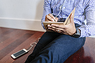 Man sitting on the wooden floor writing a note - GIOF03152