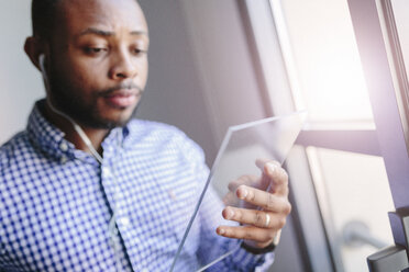 Young man using a futuristic tablet - GIOF03155