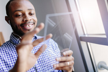 Smiling young man using a futuristic tablet - GIOF03158