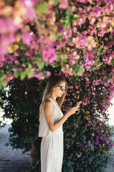 Woman using cell phone in park under pink blossoms - JPF00275