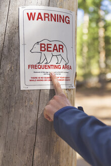 USA, Wyoming, Yellowstone National Park, hand pointing on bear warning sign - EPF00466