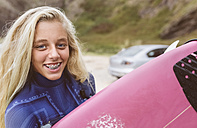 Spain, Aviles, portrait of smiling young surfer on the beach - MGOF03539