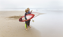 Spain, Aviles, two young surfers on the beach - MGOF03548