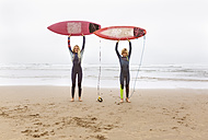 Spain, Aviles, two young surfers on the beach holding their surfboards - MGOF03554