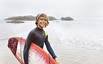 Spain, Aviles, portrait of smiling young surfer carrying surfboard on the beach - MGOF03563