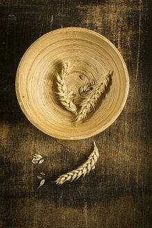 Wheat ears and grains on wooden bowl and wood - MAEF12393