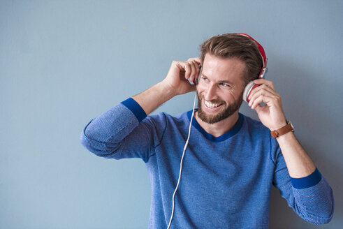Smiling man listening to music with headphones - DIGF02717