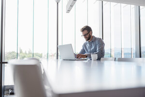 Man using laptop sitting at conference table in office - DIGF02723