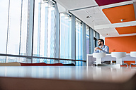 Man with coffee cup sitting in modern office building - DIGF02726