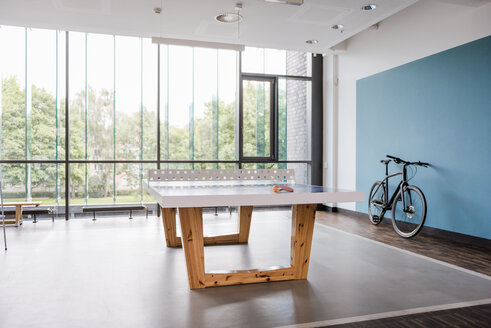 Table tennis table and bicycle in break room of modern office - DIGF02738
