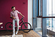 Man with bicycle standing in modern office looking out of window - DIGF02741