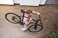 Man with bicycle walking in office - DIGF02747