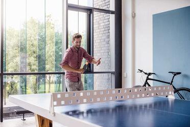 Man in break room of modern office playing table tennis - DIGF02750