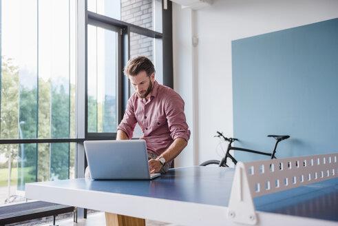 Man using laptop in break room of modern office on table tennis table - DIGF02753