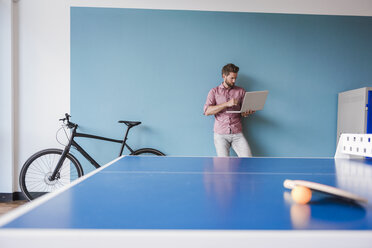 Man using laptop in break room of modern office - DIGF02756
