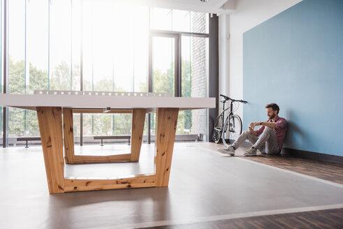 Man sitting on the floor in break room of modern office - DIGF02759