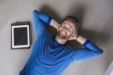 Smiling man lying on the floor next to tablet - DIGF02762