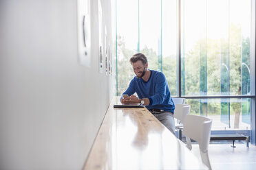 Smiling man looking at cell phone on table by the window - DIGF02765