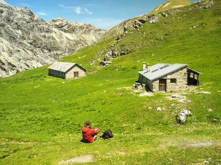 Italy, Lombardy, Sondrio, hiker resting on alpine meadow on the way to Umbrail Pass - LAF01882