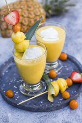 Two glasses of tropical smoothie with pineapple, mango, coconut milk and coconut flakes - YFF00671