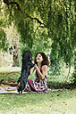Woman with dog having a picnic in a park - ALBF00154