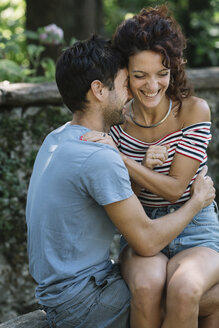 Couple in love hugging on bench in a park - ALBF00160
