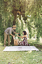Couple preparing a picnic in a park - ALBF00163