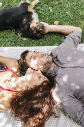 Couple in love with dog lying on a blanket - ALBF00169