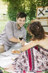 Couple having a picnic in a park drinking red wine - ALBF00175