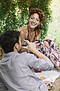 Couple having a picnic in a park drinking red wine - ALBF00178