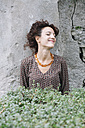 Smiling woman wearing elegant dress leaning against a wall - ALBF00181