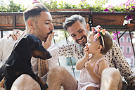 Happy gay couple with daughter and dog on balcony - MRAF00223