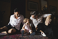 Happy gay couple with daughter and dog at home - MRAF00226